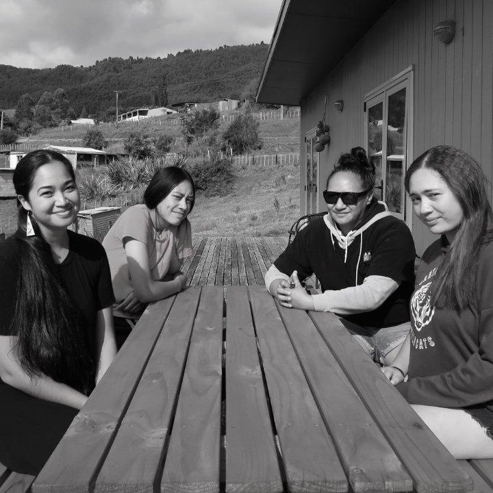 Three Women Staff Seated With Momi Afelin Of Hawaii At Table Outside Manawa Honey Office, Ruatāhuna, Te Urewera, NZ